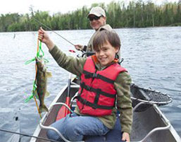 Possum Lodge Cabins - Photo of a man and boy fishing on a boat.