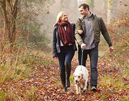 Possum Lodge Cabins - A photo of a man and woman walking a dog on a wooded path. Possum lodge is your romantic Ohio cabin getaway.